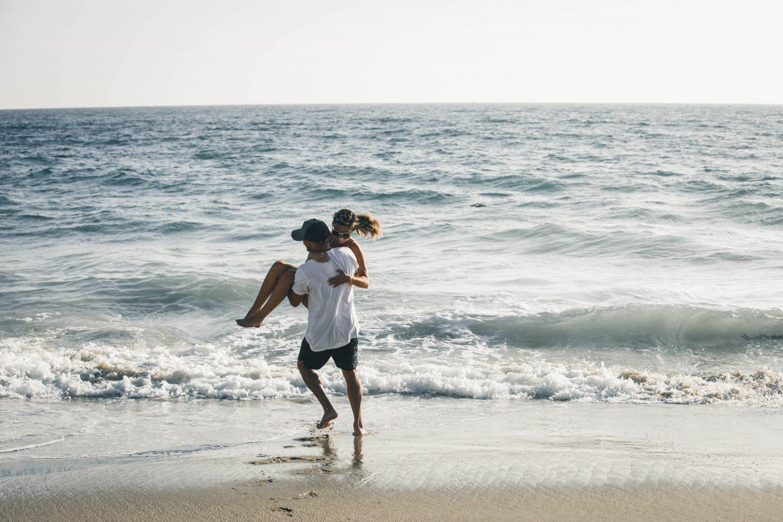 man carrying woman on seashore