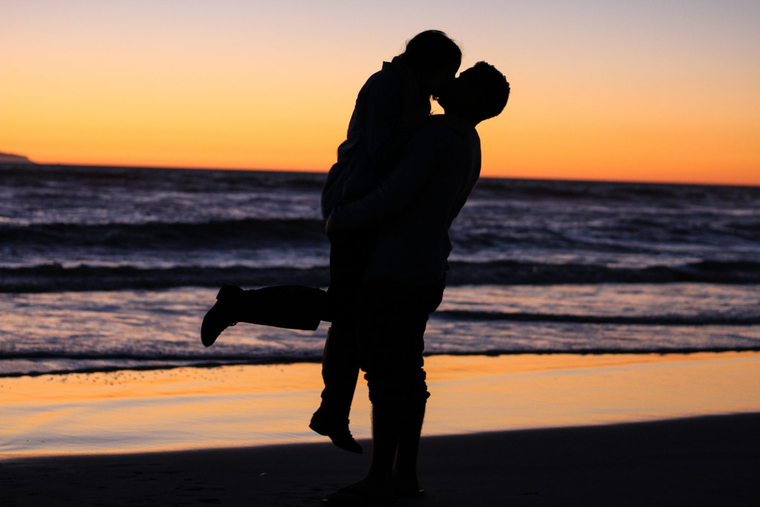 silhouette photo of couple kissing near sea during golden hour