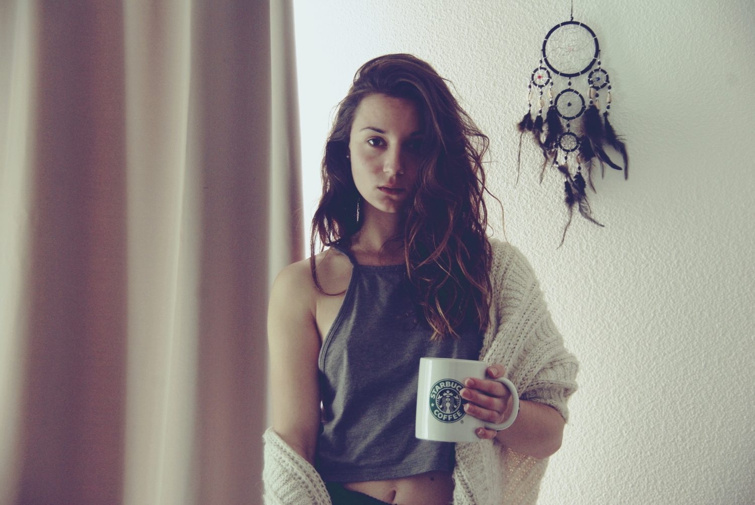 woman in gray halter top holding mug