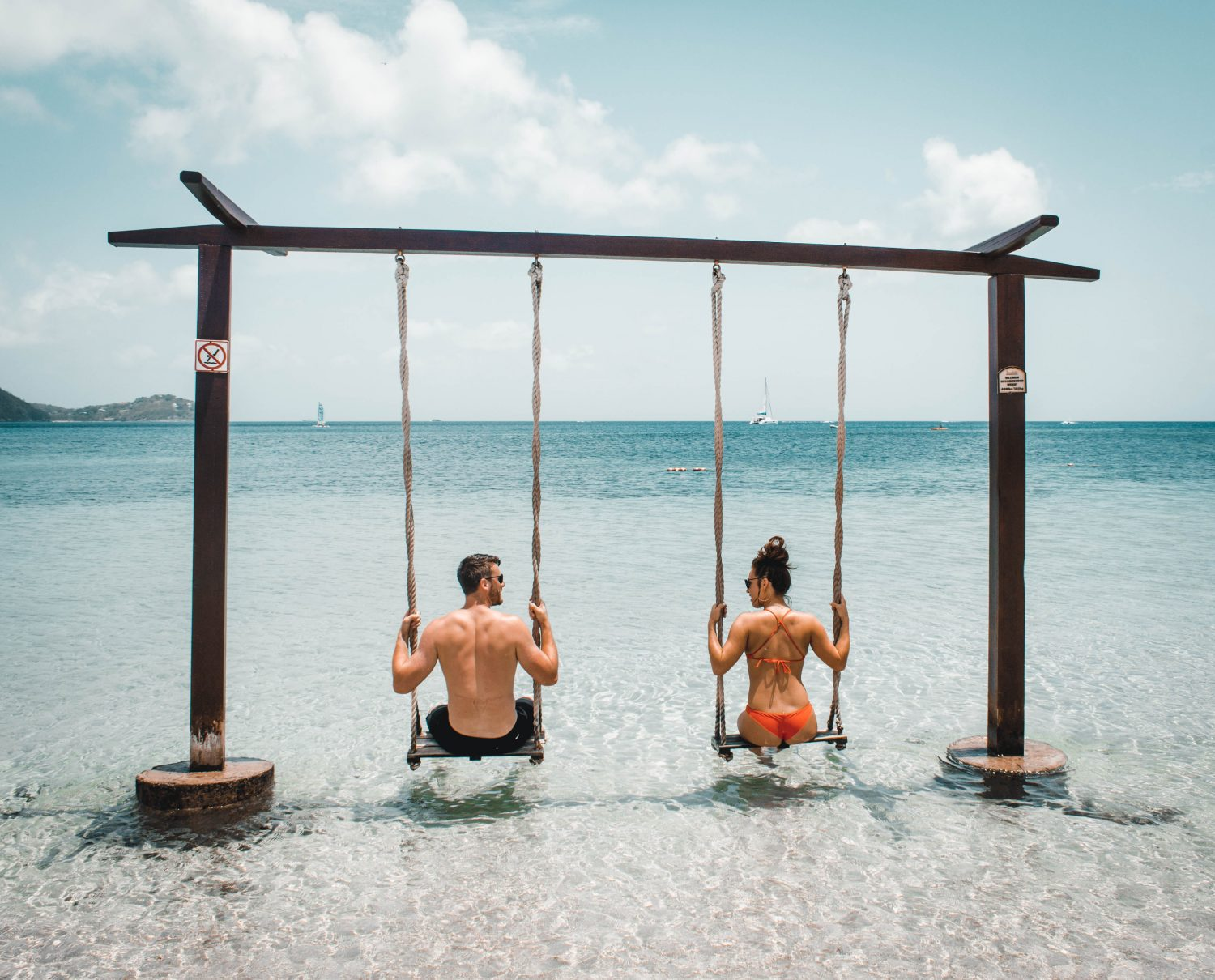 man and woman on swing on body of water