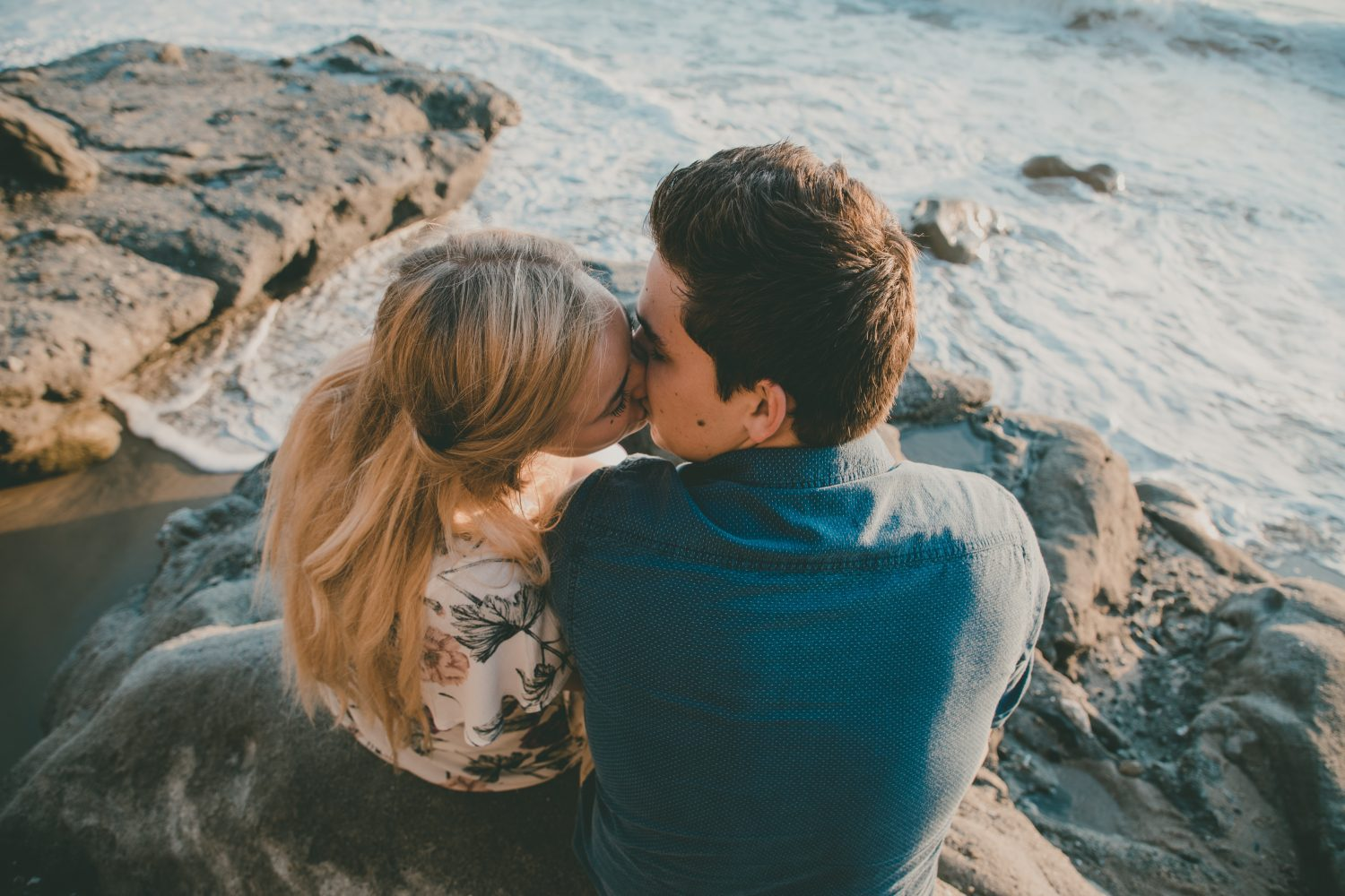 couple kissing white sitting on rock at the beach