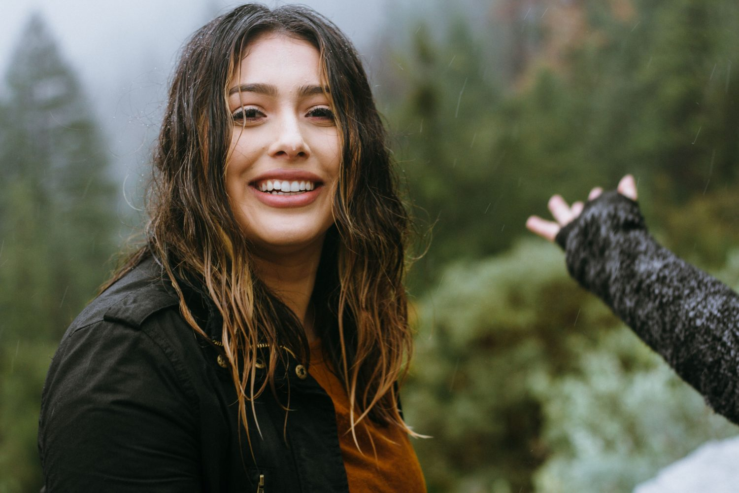 woman wearing black jacket smiling with forest background