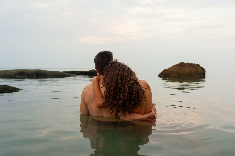 topless man sitting on water during daytime